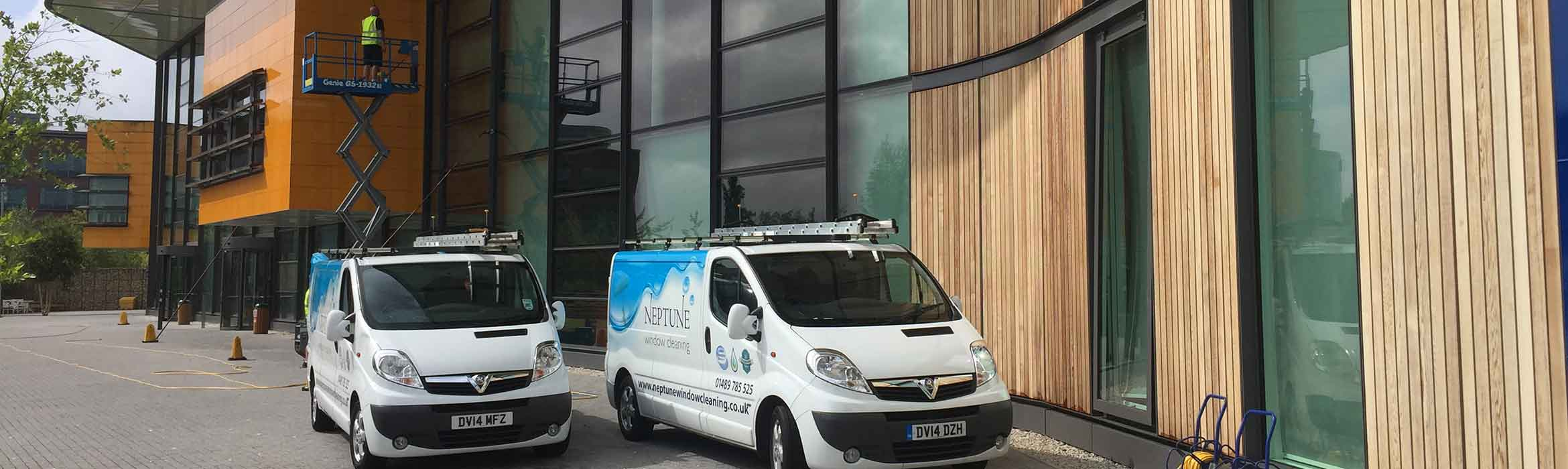 Two Neptune Window Cleaning vans and a scissor lift cleaning B&Q head office exterior.