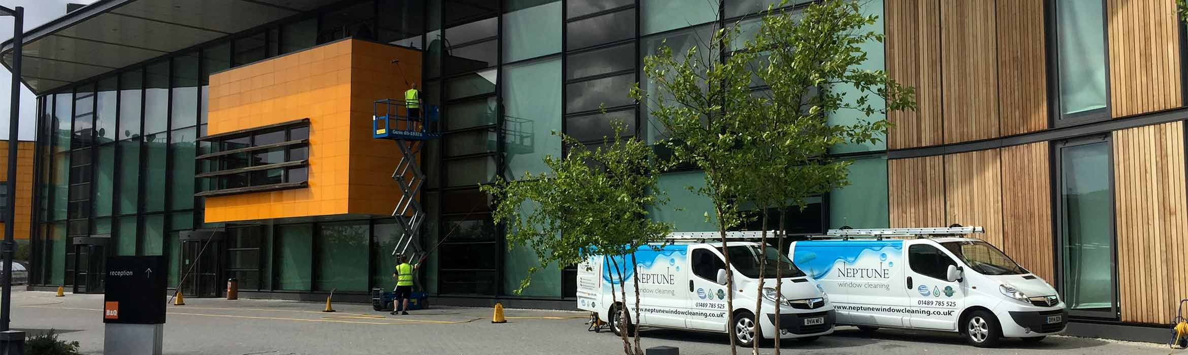 Front elevation of B&Q Head Office with two Neptune Window Cleaning vans in operation with window cleaner working from a scissor lift platform.