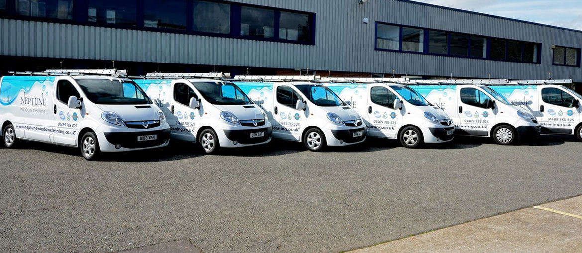 Six distinctive liveried Neptune Window Cleaning vans lined up in a neat row. They are white with the distictive aqua blue Neptune logo wave design. The image caption says, Neptune Window Cleaning, the capacity to clean up.